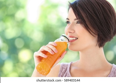 Young beautiful woman with bottle of orange juice outdoor
