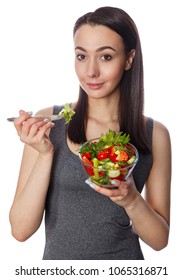 Young beautiful woman and a bowl of salad with fresh vegetables isolated on white background