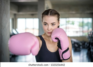 Young beautiful woman with boxing gloves exercise in fitness gym.