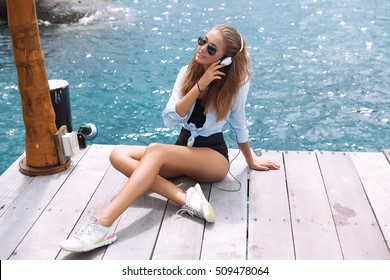 Young beautiful woman in bright outfit enjoying the music at summer background.Maldives ,island summer girl,young sexy hipster wear denim shirt,listening music,headphones,smartphone,smiling laughing