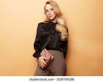 young beautiful woman in a brown blouse and pants holds a handbag and posing on a beige background.