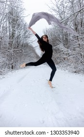 Young beautiful woman brown-haired girl in black ballet suit jumps and dances peak in snowy winter forest