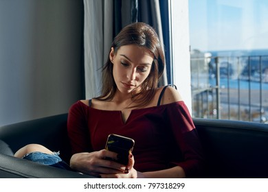 Young beautiful woman browsing smartphone while chiling in armchair against window.