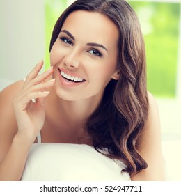Young beautiful woman brunette waking up with pillow, at bedroom. Healthy lifestyle and happiness concept.