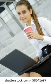 Young, beautiful woman business over coffee in the fresh air sitting on the stairs, office building, next to the laptop