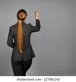 Young beautiful woman in business suit writing with chalk on grey background. Back view.