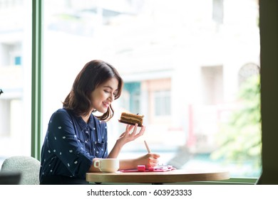 Young beautiful woman in the cafe near the window, thinking and writing something with cake in hand.