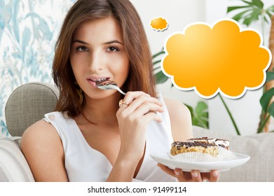 Young beautiful woman with a cake. Closeup portrait. Sitting on sofa at her home. Blank cloud balloon for her thoughts.