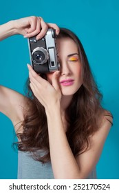 Young beautiful woman with a camera on a blue background. Model. Photographer.