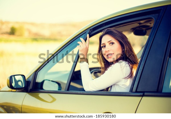 Young beautiful woman in car at the drivers seat