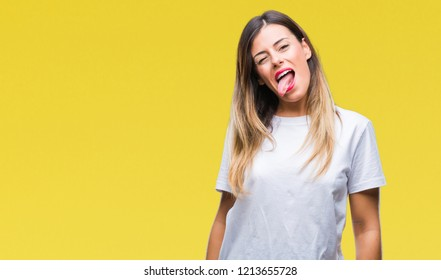 Young beautiful woman casual white t-shirt over isolated background sticking tongue out happy with funny expression. Emotion concept.