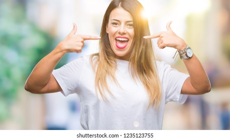 Young beautiful woman casual white t-shirt over isolated background smiling confident showing and pointing with fingers teeth and mouth. Health concept.