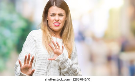 Young beautiful woman casual white sweater over isolated background disgusted expression, displeased and fearful doing disgust face because aversion reaction. With hands raised. Annoying concept.
