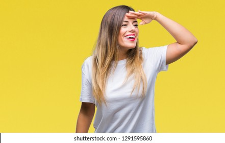 Young beautiful woman casual white t-shirt over isolated background very happy and smiling looking far away with hand over head. Searching concept.