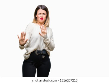 Young beautiful woman casual white sweater over isolated background afraid and terrified with fear expression stop gesture with hands, shouting in shock. Panic concept.