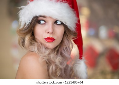 Young beautiful woman celebrates Christmas at home in the interior with a Christmas tree, gifts, a fireplace, in a Santa Claus hat