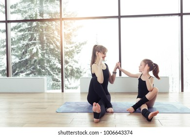 Young beautiful woman and charming little daughter are doing difficult yoga exercises and smiling while working out at gym with beautiful scenery outside window with sunlight. Healthy fitness concept