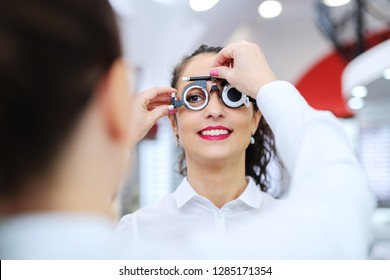 Young beautiful woman checking her sight at ophthalmologist. On eyes phoropter.