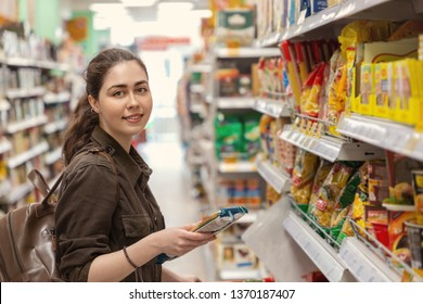 Young beautiful woman chooses products in the supermarket.