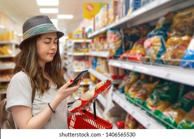 Young beautiful woman chooses products in the supermarket and checks the QR code on the label. The concept of modern technology and shopping in the store. Tint.