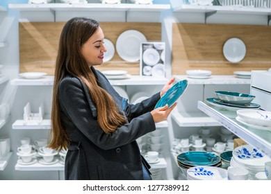 young beautiful woman choosing dinner utensil plate dishes in a store supermarket shop.