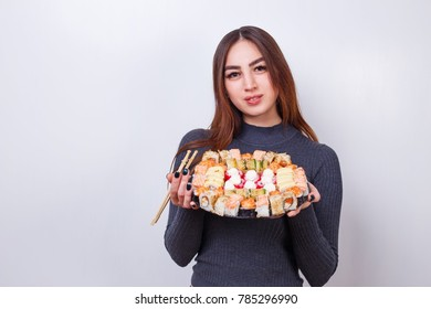 Young beautiful woman with chopsticks and sushi set, studio shoot on white background with copy space. Japanese food