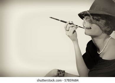 Young beautiful woman with  cigarette in mouthpiece in hat with veil