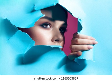 Young beautiful woman with clean perfect skin through gap in cardboard. Beauty portrait