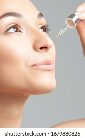 Young beautiful woman with clean perfect skin uses age-sensitive serum in pipette. Skin care and age cosmetics