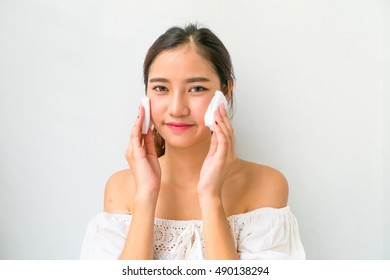 young beautiful woman cleaning face by cotton