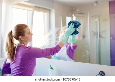 Young beautiful woman cleaning mirror in bathroom. Cleaning service. Maid cleaning at home