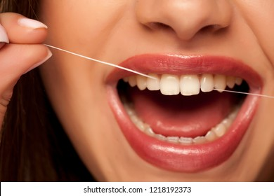 young beautiful woman cleans her teeth with dental floss