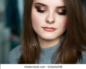 Young beautiful woman with closed eyes professional make up and hairstyle with domestic room blurry background