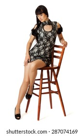 Young beautiful woman in cocktail dress is sitting on high wooden chair.