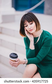 Young beautiful woman with coffee to go posing in the city