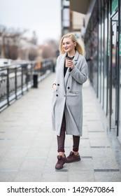Young beautiful woman with coffee walking in street