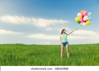 Young beautiful woman with colorful balloons on a green meadow