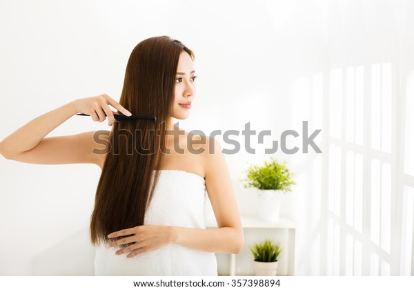 young beautiful woman combing her hair  in living room