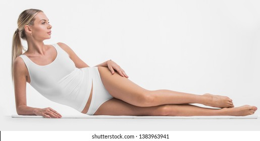 Young beautiful woman in cotton underwear lying on white background
