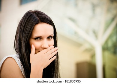 Young beautiful woman covering mouth with hand