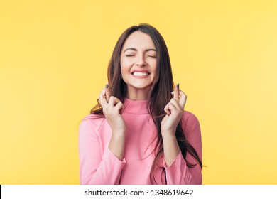 Young beautiful woman crossing her fingers and wishing for good luck over yellow background. Hope and wishing concept