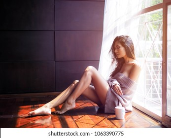 Young beautiful woman with cup of coffee sitting down by the window.