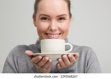 Young beautiful woman with a cup of fresh coffee in her hand
