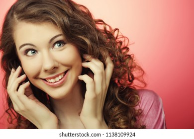 young beautiful woman with curly hair over pink background