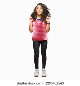 Young beautiful woman with curly hair wearing stripes t-shirt amazed and surprised looking up and pointing with fingers and raised arms.