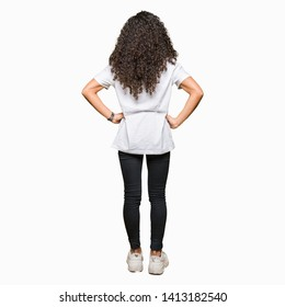 Young beautiful woman with curly hair wearing white t-shirt standing backwards looking away with arms on body