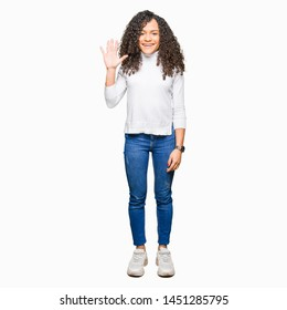 Young beautiful woman with curly hair wearing turtleneck sweater showing and pointing up with fingers number five while smiling confident and happy.