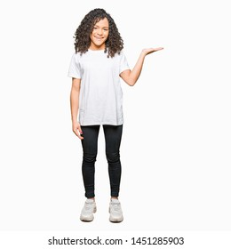 Young beautiful woman with curly hair wearing white t-shirt smiling cheerful presenting and pointing with palm of hand looking at the camera.