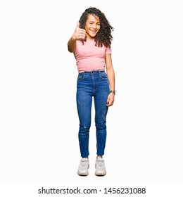 Young beautiful woman with curly hair wearing pink t-shirt doing happy thumbs up gesture with hand. Approving expression looking at the camera showing success.