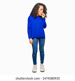 Young beautiful woman with curly hair wearing winter sweater feeling unwell and coughing as symptom for cold or bronchitis. Healthcare concept.